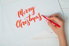 Enhorabuena de la Feliz Navidad El calígrafo escribe con tinta roja en la tarjeta blanca calligraphy Fuente del ornamento El arte imágenes de archivo libres de regalías