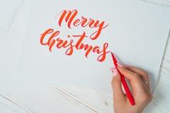 Enhorabuena de la Feliz Navidad El calígrafo escribe con tinta roja en la tarjeta blanca calligraphy Fuente del ornamento El arte fotos de archivo