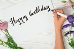 Enhorabuena del feliz cumpleaños El calígrafo escribe con tinta negra en la tarjeta blanca calligraphy Fuente del ornamento El ar foto de archivo