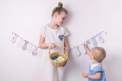 Enhorabuena en Pascua feliz: la muchacha está sosteniendo una cesta con los huevos pintados al lado de la pared blanca imagenes de archivo