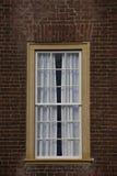 Enig geel ontworpen venster op rode bakstenen muur. Stock Fotografie
