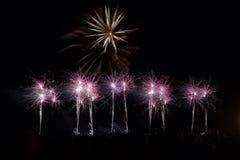 Enig vuurwerk boven verscheidene kleinere slepen en explosies Stock Afbeelding