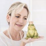 Enige aantrekkelijke oudere vrouw met een kikkerkoning in haar handen Stock Foto's