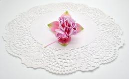 Enige bloem van fuchsiakleurig roze op een witte achtergrond op een servet Stock Foto
