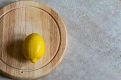 Enige citroen op scherpe raad met tan steenachtergrond stock foto