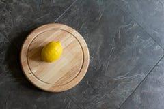 Enige citroen op scherpe raad tegen grijze steenachtergrond royalty-vrije stock afbeeldingen