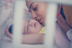 Enige moeder die haar kussen weinig baby in slecht Sluit omhoog royalty-vrije stock foto