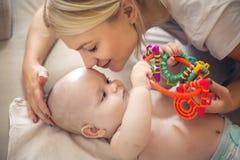 Enige moeder die met haar weinig baby spelen stock foto