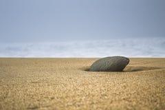 Enige steen in zand op het strand Stock Afbeelding