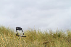 Enige stoelzitting in grasrijke zandduinen Royalty-vrije Stock Fotografie