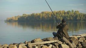 Enige vissers gietende hengel, die op vissen, mooie aard, hobby wachten stock footage