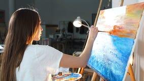 Enige vrouwenkunstenaar die beeld op canvas met olieverven in workshop veroorzaken stock video
