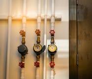 Enige watermeter en rode kleppen op witte concrete muur van huis Waterverbruik en rekeningsconcept Geïnstalleerde watermeters stock fotografie