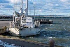 Enige witte varende die boot, bij haven wordt vastgelegd royalty-vrije stock afbeelding