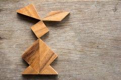 Enigma chinês do tangram na forma do coelho no engodo de madeira do fundo fotografia de stock royalty free