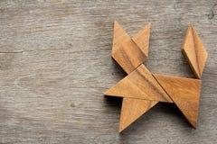 Enigma chinês do tangram na forma do gato no fundo de madeira imagem de stock royalty free