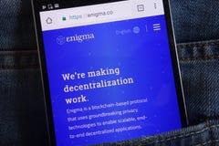 Enigma-cryptocurrencywebsite op smartphone wordt getoond in jeanszak die wordt verborgen stock foto