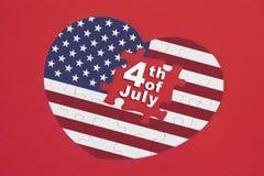 Enigma de serra de vaivém da bandeira de América da forma do coração com uma palavra escrita 4o julho Foto de Stock