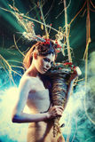 Enigma woman. Art project. Beautiful girl in the image of a wild deer stands in a deserted forest Stock Photos