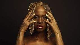 Enigmatic african american female model with golden glossy makeup and headwear posing for camera. High fashion Vogue. Concept stock footage