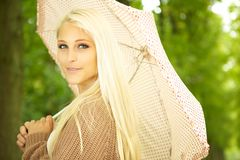 Enigmatic Beauty With Umbrella. Beautiful blonde female model posing in park under polka dot umbrella Royalty Free Stock Image