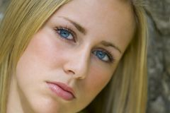Enigmatic Blonde. A beautiful young blonde woman stares enigmatically into the camera Royalty Free Stock Photography