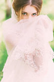 Enigmatic bride covering face with veil. On nature Royalty Free Stock Photography