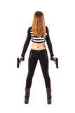 Enigmatic female spy with guns. Enigmatic and instigant female spy with hair over face is holding two guns in her hands pointed downwards - isolated on white Royalty Free Stock Image