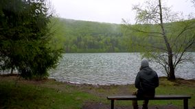 Enigmatic lonely man sitting on bench on lake shore in the mountain forest. Rainy day beautiful mountain lake shore in Norway. Sca. Ndinavian landscape. Rainy stock video