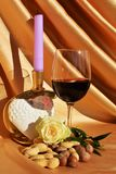 Enigmatic love. The golden folds of soft textured fabric create a mysterious atmosphere and the rose, the candle, the heart shaped object and the glass of wine Royalty Free Stock Photo