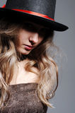 Enigmatic woman. Beauty enigmatic woman in black top hat isolated on grey Royalty Free Stock Photography