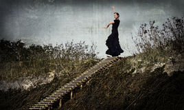 Enigmatic woman in black dancing in the dunes, on the top of the stairs Royalty Free Stock Images