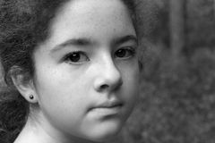Enigmatic Young Girl B&W. A teenaged girl, staring toward the camera with an enigmatic expression stock photo