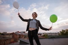 Enigmatic young woman with two toy balloons. Dreamy and infantile personality, airiness and hope, fly to dreams and rich imagination concept. Uban city Royalty Free Stock Image