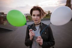 Enigmatic young woman with two toy balloons. Close up. Party and celebration, walk around the city, hope and infantile personality concept Stock Photography