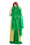 Enigmatic young woman. Wearing luxury green dress. Isolated on white Stock Photography