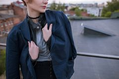 Enigmatic young woman wearing in man`s jacket. On urban city background. Close up of tenderness and romance, melancholy and love concept Royalty Free Stock Images
