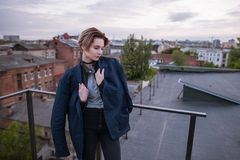 Enigmatic young woman wearing in man`s jacket. On urban city background. Meeting on roof, tenderness and romance, melancholy and love concept Stock Image