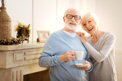 Enigmatical bearded man standing near his wife. Funny joke. Attractive pensioner keeping smile on his face and holding cup while looking forward royalty free stock image