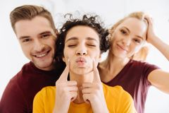 Enigmatical girl pointing at her cheeks. Kiss me. Handsome male person keeping smile on his face and standing near his friends while looking at camera Stock Photography