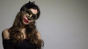 Enigmatyczna brunetki kobieta jest ubranym karnawał maski pozy przeciw szaremu tłu 4K wideo zdjęcie wideo