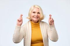 Enior caucasian kobiety uśmiechnięty skrzyżowanie dotyka z nadzieją i oczami zamykającymi zdjęcie stock