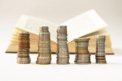 Enjeux des pièces de monnaie un livre ouvert photographie stock