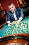 Enjeux souriants de joueur jouant la roulette Photo stock