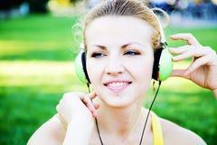 enjoing户外音乐的年轻快乐的妇女 免版税库存图片