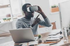 Enjoing innovation technologies. Good looking young African man in virtual reality headset pointing in the air while sitting at the desk in creative office Royalty Free Stock Photo