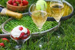 Enjoing in Wimbledon tennis championship with champagne and strawberries with cream. Wimbledon symbols on green grass stock photography
