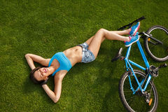 Enjoing. The woman lies on the grass in the Park and enjoy the summer sun Stock Photography