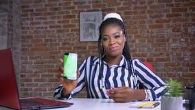 Enjouable biznesowej kobiety przedstawień zieleni afrykański ekran szczęśliwie i uśmiechy i relaksujący przy biurkiem obok ściana