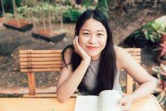 Enjoy放松与美丽泰国青少年读一本书的阅读书亚裔妇女的时期 图库摄影